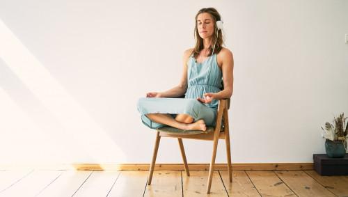 Eine Frau sitzt meditierend auf einem Stuhl