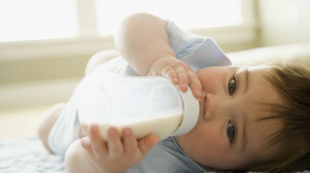 Ein Baby liegt auf einem Bett und trinkt Milch aus dem Fläschchen.