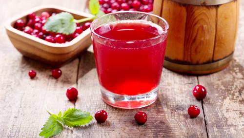 Ein Glas Cranberrysaft und Schalen mit den Beeren stehen auf einem Tisch