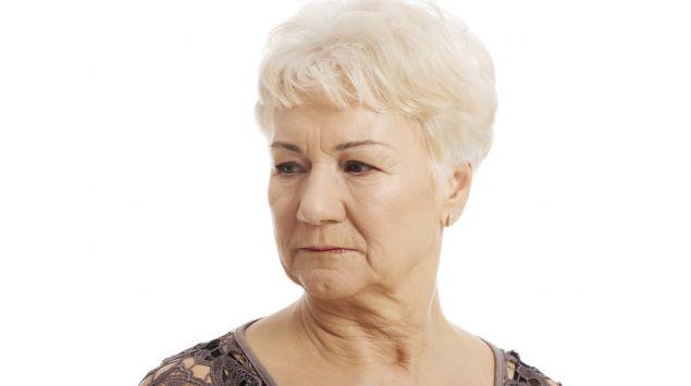 Ältere Frau mit Kinnfalten schaut zur Seite