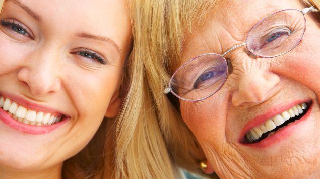 Großmutter und Enkelin lachen in die Kamera