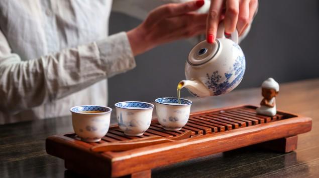 Eine Frau gießt grünen Tee auf.