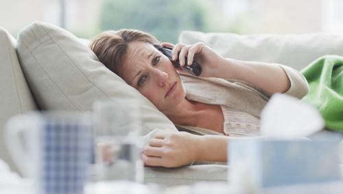 Eine Frau liegt krank auf dem Sofa und telefoniert.