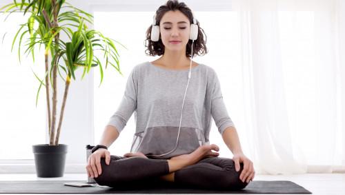 Eine Frau meditiert mit Kopfhörer