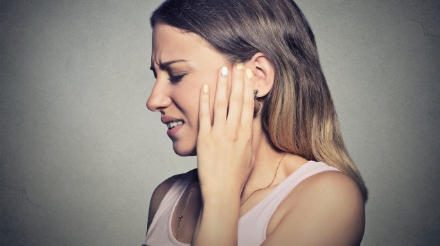 Trigeminusneuralgie: Eine Frau hält sich eine Hand an die schmerzende Wange.