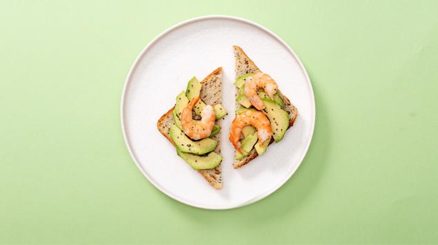 Toastbrot auf Teller mit Avocado und Shrimps