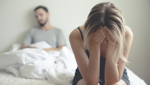Ein Paar sitzt traurig im Bett