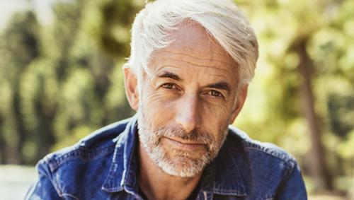 Ein älterer Mann in blauem Jeanshemd schaut gerade in die Kamera.