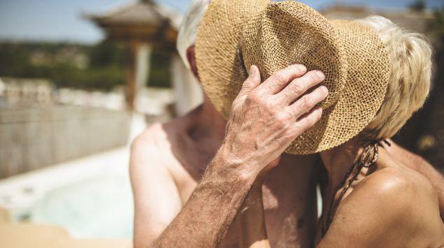 Senioren-Paar versteckt sich am Strand küssend hinter dem Hut