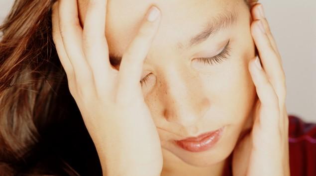 Eine Frau stützt ihren Kopf mit den Händen ab und wirkt abgeschlagen.