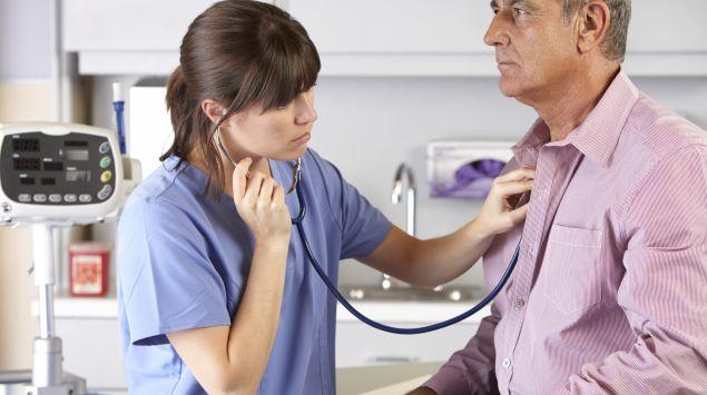 Eine Ärztin hört einen Mann mit einem Stethoskop ab.
