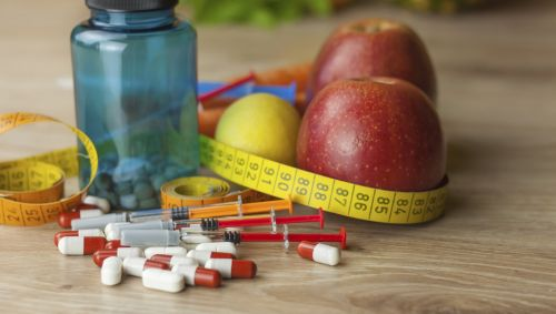 Das Bild zeigt verschiedene Pillen, zwei Äpfel und ein Gefäß.