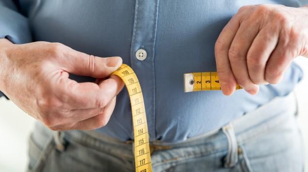 Ein übergewichtiger Mann legt ein Maßband um seinen Bauch.