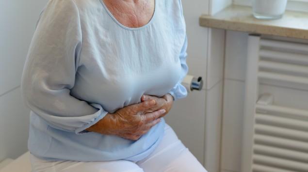 Eine ältere Frau hält sich den Bauch, weil die Divertikel im Darm Beschwerden bereiten.