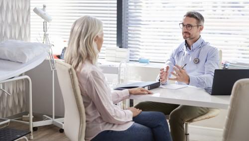 Eine ältere Frau im Gespräch mit einem Arzt.