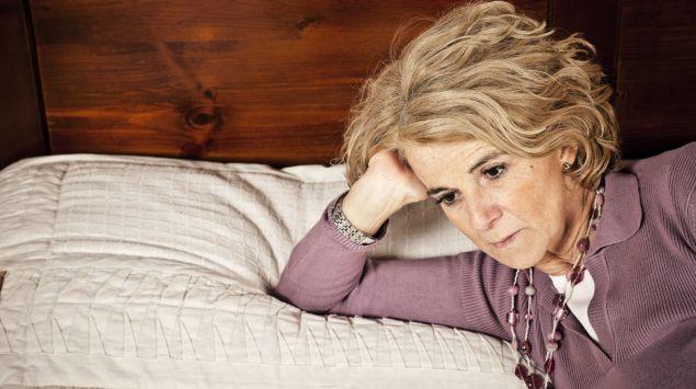 Eine nachdenklich wirkende ältere Frau auf einem Bett.