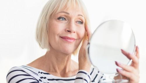 Eine ältere Frau schaut in den Vergrößerungsspiegel