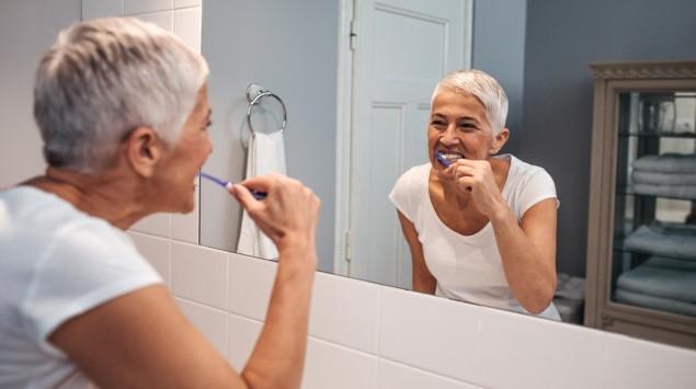 Eine ältere Frau putzt sich vorm Spiegel die Zähne.