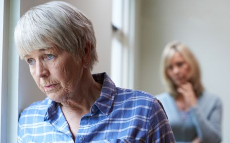 Eine traurig wirkende Seniorin und im Hintergrund eine jüngere Frau, die sorgenvoll dreinblickt.