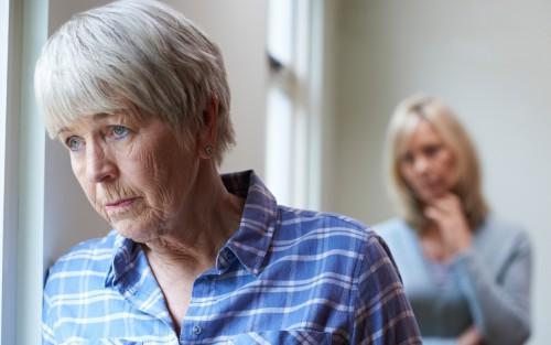 Eine traurig wirkende Seniorin guckt aus dem Fenster; hinter ihr steht eine jüngere Frau, die sorgenvoll derinblickt.