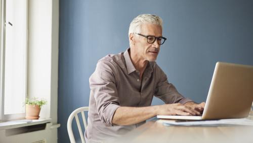 Ein älterer Mann vor seinem Laptop.