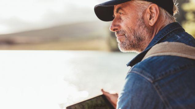 Das Bild zeigt einen älteren Mann, der mit einem Tablet am See ist.