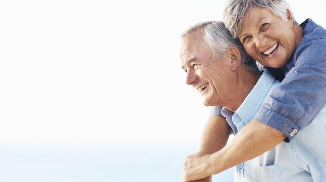 Zu sehen ist ein vergnügtes älteres Paar am Meer.