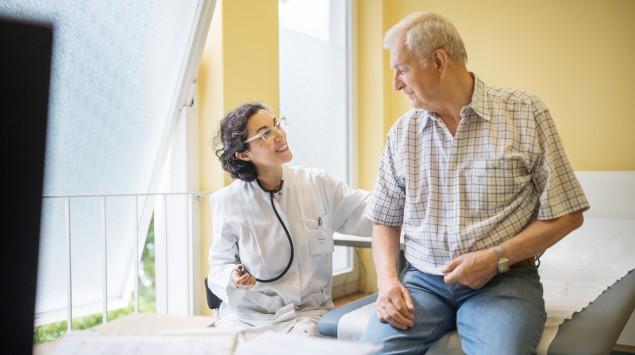 Eine Ärztin mit einem älteren Patienten.