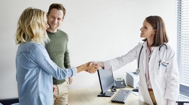 Eine Ärztin begrüßt ein junges Paar.