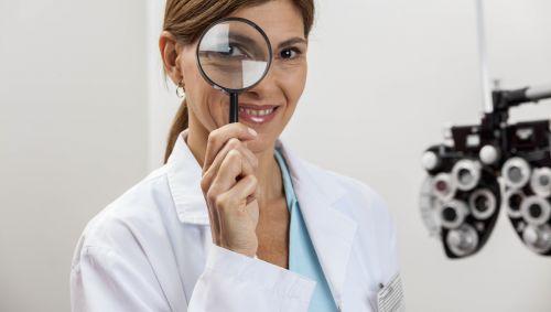 Eine Ärztin schaut durch eine Lupe.