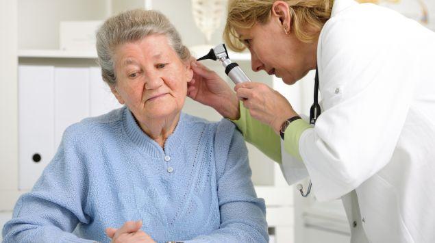 Eine Ärztin schaut in das Ohr einer älteren Patientin.