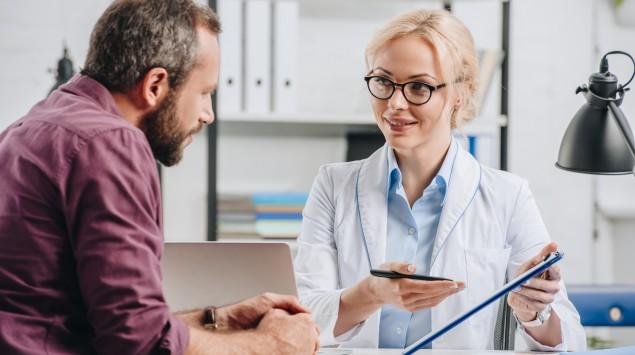 Eine Ärztin erklärt ihrem Patient etwas