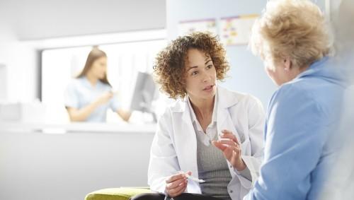 Eine junge Ärztin im Gespräch mit einer Seniorin.