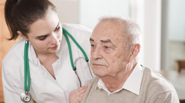 Eine junge Ärztin fasst einem älteren Mann besorgt an die Schulter.