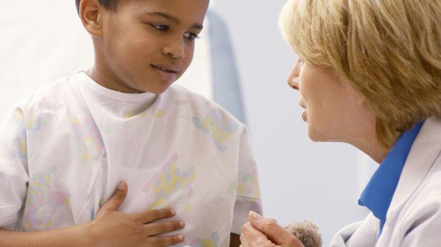 Eine Ärztin unterhält sich mit einem kleinen Jungen.
