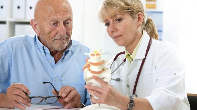Ein älterer Mann sitzt neben einer Ärztin, die einen Teil eines Wiebelsäulenmodells in der Hand hält und mit der anderen Hand darauf deutet.