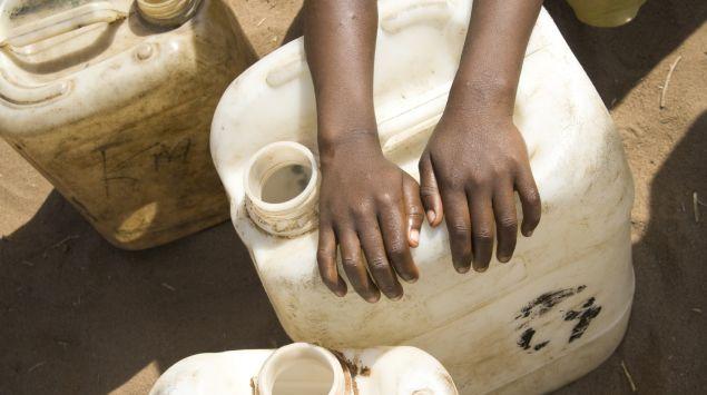 Ein Kind legt seine Hände auf einen Wassercontainer.