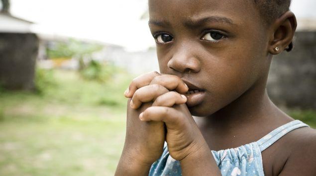 Ein afrikanisches Mädchen mit traurigem Gesichtsausdruck hält ihre gefalteten Hände vor ihren Mund.