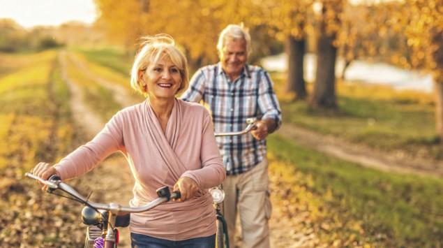 Man sieht einen älteren Mann und eine ältere Frau mit Fahrrädern in herbstlicher Umgebung.