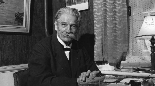 Albert Schweitzer sitzt an einem Tisch.