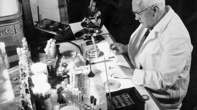 Foto aus dem Jahr 1954 von Sir Alexander Fleming, der in einem Labor an einem Tisch sitzt.