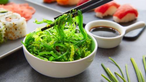 Jemand isst mit Stäbchen Algensalat aus einer Schale; daneben stehen Sushi-Platten und ein Schälchen Sojasauce.