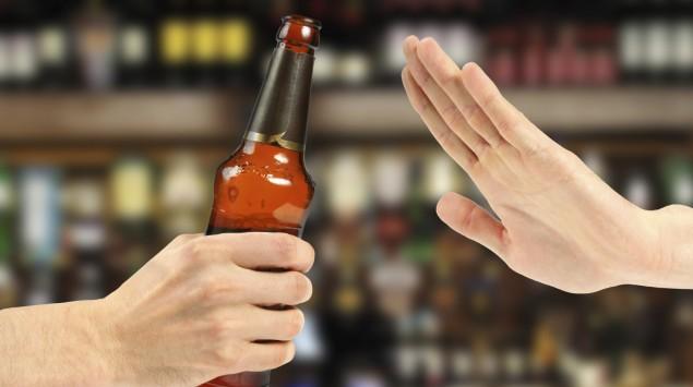 Jemand lehnt mit einer Handbewegung eine ihm angebotene Bierflasche ab.