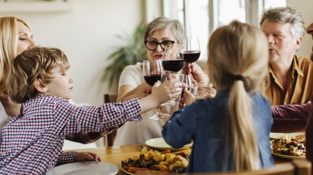 Eine Familie stößt mit Rotwein an.