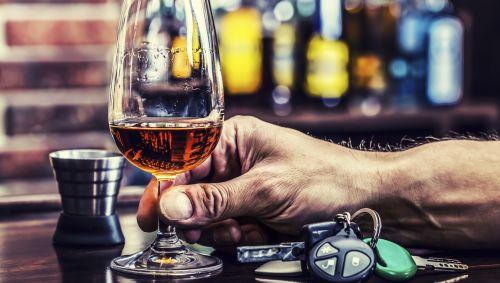 Das Bild zeigt ein Glas Brandy und einen Autoschlüssel auf einer Bar.