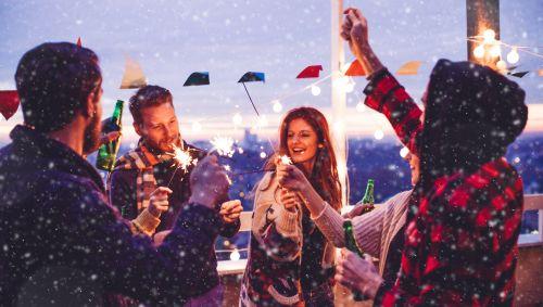 Das Bild zeigt eine Gruppe junger Erwachsener mit Wunderkerzen und Alkohol.