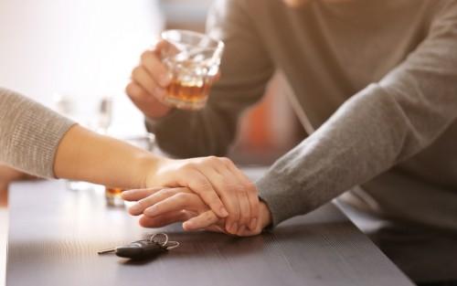 Eine Frau hintert einen Alkohol trinkenden Mann daran, nach einem Autschlüssel zu greifen.