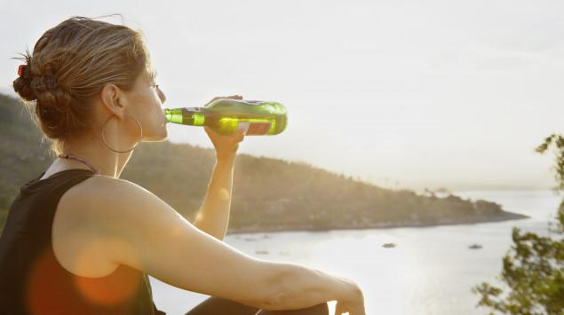 Eine Frau sitzt am Wasser und trinkt ein Bier.