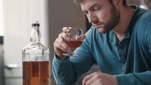 Ein Mann trinkt hochprozentigen Alkohol.