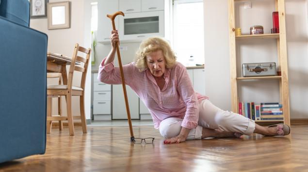eine alte Frau sitzt nach einem Sturz auf dem Boden